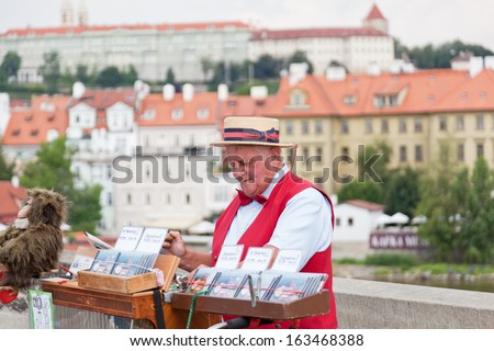 PRAGUE, CZECH REPUBLIC - JULY 30: Man offers music from hand operated music box in exchange for money on Charles Bridge on July 30, 2013 in Prague, Czech Republic