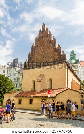 PRAGUE, CZECH REPUBLIC - JULY 17, 2014: Tourists in front of the Old New Synagogue, in the Josefov district. The building its the first gothic building of Prague, finished in 1270. - stock photo