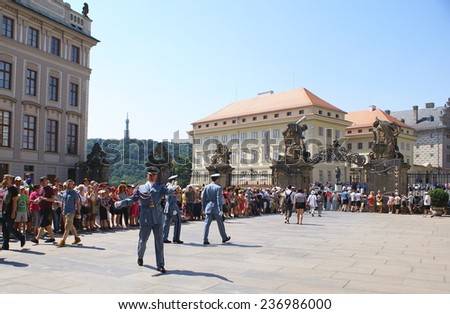 PRAGUE, CZECH REPUBLIC  - JULY 19, 2014. Tourists in the First Courtyard of the Prague Castle. Giants' Gate - sculptures of fighting giants from 1768 at the  entrance of Prague Castle ,Czech Republic. - stock photo