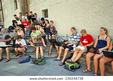 PRAGUE, CZECH REPUBLIC - JULY 31: Young students working on laptop, outdoor lesson on July 31, 2008 in Prague, Czech Republic. - stock photo