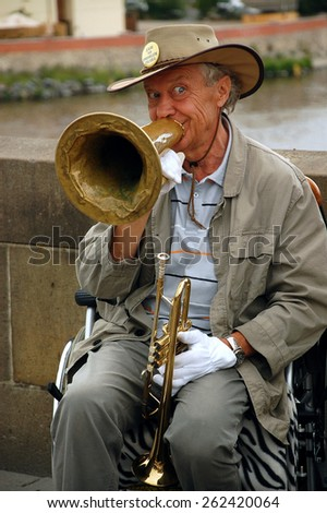 PRAGUE, CZECH REPUBLIC - JUNE 14, 2008: Famous in Prague stiff-limbed street musician plays jazz on the Charles bridge in the capital of Czechia Prague while sitting on the wheel chair - stock photo