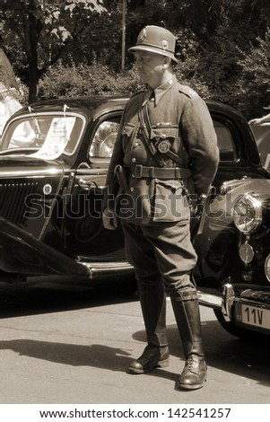 PRAGUE, CZECH REPUBLIC - JUNE 15: Parade of The Prague Club of Historic Cars, A police officer in the historical clothing of 20s-40s, on June 15, 2013 in Prague, Opletalova Street, Czech Republic.