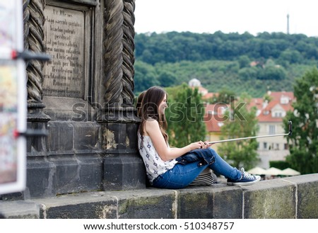 Prague, Czech Republic - June 26: The girl sit on the Charles Bridge and take the selfie on June 26, 2015 in Prague, Czech Republic.