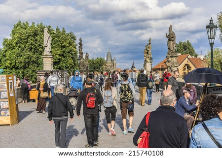 PRAGUE, CZECH REPUBLIC - JUNE 20, 2014: Tourists walking along Charles Bridge while sightseeing historical capital of the Czech Republic. Charles Bridge (Karluv most, 1357) - a famous historic bridge.