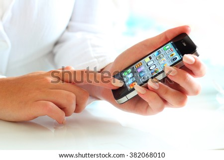 Prague, Czech Republic - June 10, 2012: Woman holding iPhone in the hand. iPhone was created and developed by the Apple inc.