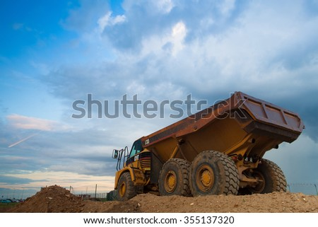 Prague Czech Republic - June 14, 2011:Yellow Cut truck on the highway construction before heavy storm. The Cat brand is the cornerstone of the Caterpillar brand portfolio. - stock photo
