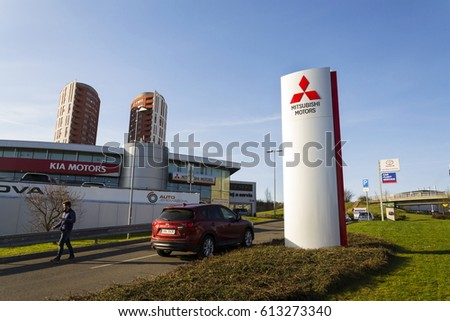 PRAGUE, CZECH REPUBLIC - MARCH 31: Mitsubishi motors company logo with Mazda car in front of dealership building on March 31, 2017 in Prague, Czech republic.