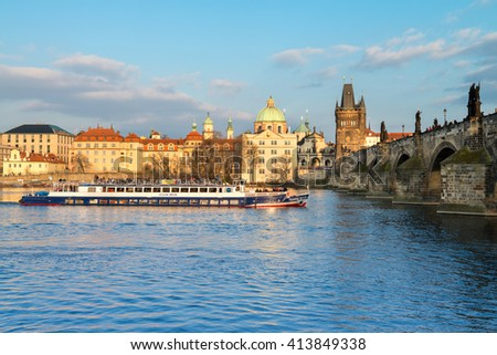 PRAGUE, CZECH REPUBLIC - MARCH 26, 2016: Passenger boat goes under Charles Bridge on Vltava river in central Prague.  Prague - one of the most beautiful cities in Europe, a popular tourist center.