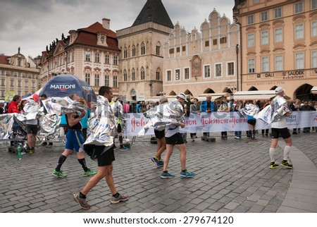 PRAGUE, CZECH REPUBLIC - MAY 3, 2015: Runners who have just finished the Volkswagen Prague Marathon wrapped in warming aluminum foil walking from the finish in the famous Old Town Square, Prague - stock photo