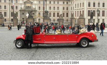Prague, Czech Republic - November 9, 2014: The driver opening a hood and looking inside the car, checking if everything is good with the touristic car. Central square of Prague - stock photo
