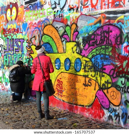 PRAGUE, CZECH REPUBLIC - NOVEMBER 05: Woman looking at Lennon Wall since the 1980s filled with John Lennon-inspired graffiti and lyrics from Beatles songs on Nov 05, 2013 in Prague, Czech Republic