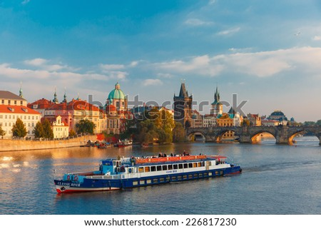 Prague, Czech Republic - October 3, 2014: Tourist boat in front Charles Bridge and Old Town in at evening. Prague - one of the most beautiful cities in Europe, a popular tourist center.  - stock photo