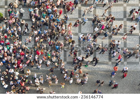 PRAGUE, CZECH REPUBLIC - SEPTEMBER 9, 2014: Top View of Large group of tourists at Prague central square looking up to Old Town Hall tower. - stock photo
