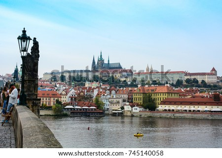 Prague, Czech Republic - September 28, 2017: Tourists walking by the Charles Bridge in Prague. View from the bridge on the Old town Cityscape of Prague, Vltava river, St. Vitus Cathedral