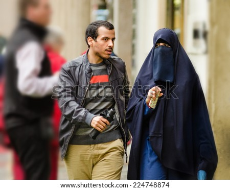 Prague, Czech Republic - September 26, 2014: Young Muslim couple walks down the street of Old Town. Woman wears traditional clothes and holding smart phone in right hand - stock photo