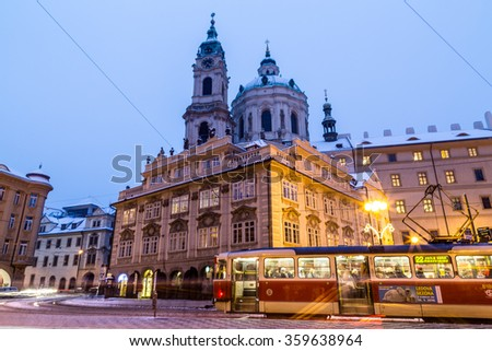 PRAGUE, CZECH REPUBLIC - 6TH JANUARY 2016: The outside of St. Nicholas Church in Prague from Malostranske Namesti at dusk. The blur of traffic and people can be seen.