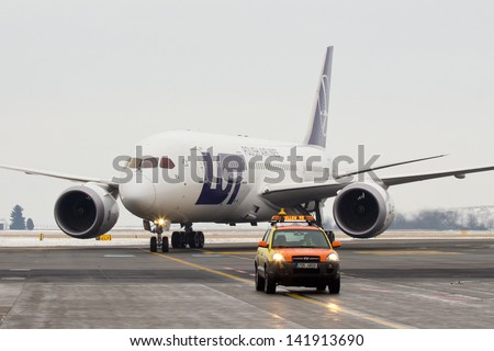 PRAGUE - DECEMBER 14: LOT Polish Airlines, Boeing B787 Dreamliner taxis for follow me car to the terminal of PRG Airport on December 14, 2012. Polish Airlines, is the flag carrier of Poland. - stock photo