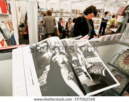 PRAGUE - MAY 15: Woman read the book of the publishing house Taschen in a book store on May 15, 2014. Association of Czech Booksellers celebrate the anniversary of the writer Bohumil Hrabal in 2014.  - stock photo
