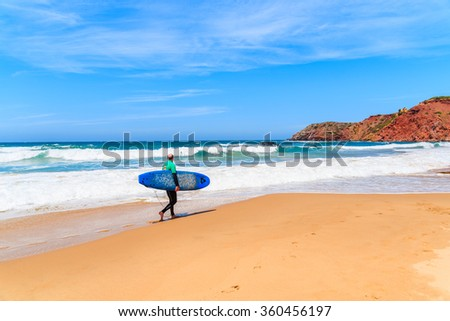 PRAIA DO AMADO BEACH, PORTUGAL - MAY 15, 2015: Surfer walking on Praia do Amado beach with ocean waves hitting shore, Algarve region, Portugal.