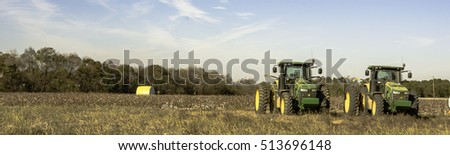 Prattville, Alabama, USA - November 5, 2016: Panoramic view of a cotton field after harvest with a wrapped bale of cotton and two John Deere Tractors.