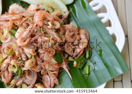 prawn spicy salad with herb on fresh banana leaf - stock photo