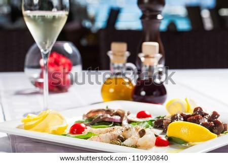 Prawns and beef blocks served with white wine. - stock photo