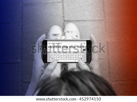 Pray for Nice, France - Woman hands sending text message with the text Praying for you, Nice - stock photo