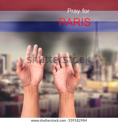 Pray for PARIS praying hands over explosion city on November 13 2015 and many people were killed across Paris with explosions attack - stock photo