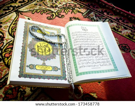 Prayer beads on the Koran - stock photo