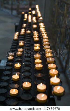 Prayer candles aka offering, sacrificial or memorial candles lit in a church - stock photo