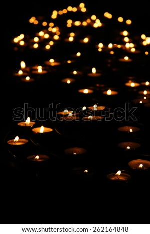 Prayer candles light up the darkness in a church - stock photo