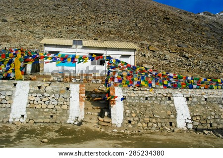 Prayer flag on Khardung La (is a high mountain pass located in the Ladakh region of the Indian state of Jammu and Kashmir) the Highest Motorable Road in the World - stock photo