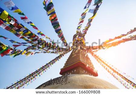 Prayer flags flying against the sun from the Boudhanath Stupa - symbol Kathmandu, Nepal. - stock photo