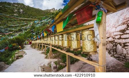 Prayer wheels near the upper temple in Chimpu Caves, Tibet, China - stock photo