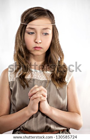 Praying and losing in thoughts beautiful young girl - stock photo