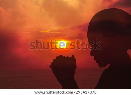 Praying at sunset - stock photo