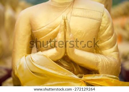 praying buddha statue  - stock photo
