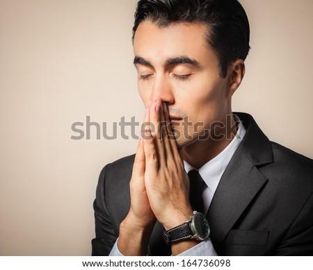 Praying businessman - stock photo