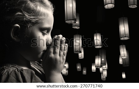Praying child On a black background full of lanterns. MANY OTHER PHOTOS FROM THIS SERIES IN MY PORTFOLIO.  - stock photo