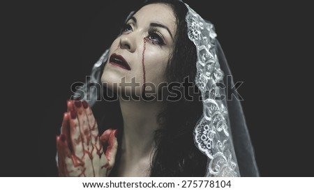 Praying, concept virgin, religion, woman with white headdress and gold crown - stock photo