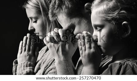 Praying family. Man, woman and child. MANY OTHER PHOTOS FROM THIS SERIES IN MY PORTFOLIO.  - stock photo