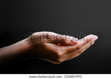 Praying female hands in black background
