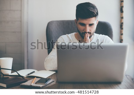 Praying for success. Front view of thoughtful young man holding hands on chin and looking at the laptop while sitting at his working place in office
