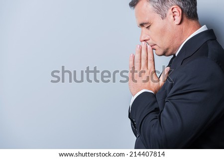Praying for success. Side view of concentrated mature man in formalwear holding hands clasped near face and keeping eyes closed while standing against grey background - stock photo