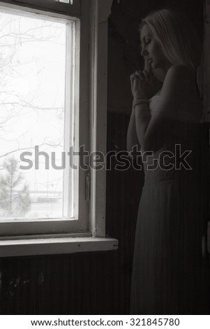 Praying ghost near the window - stock photo