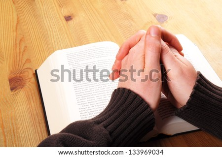 praying hand and book on desk showing religion concept - stock photo
