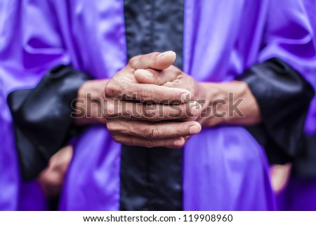 praying hand of a man wearing christian dress ready for baptism