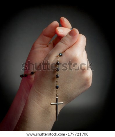 Praying Hands holding rosary beads on black background - stock photo