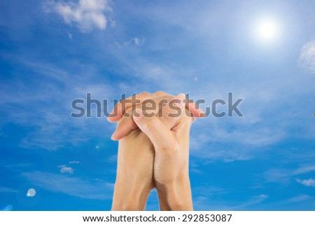 Praying Hands Isolated on sky background.
