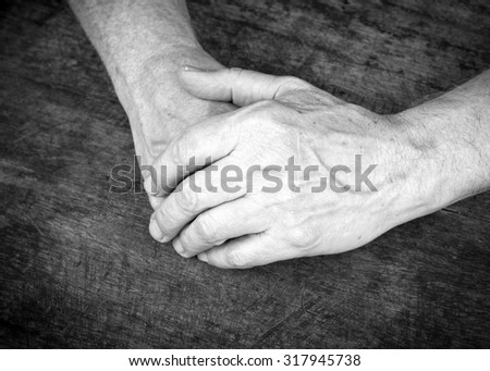 praying hands of a man on wooden table, Black and white , vignette